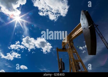 Niedrigen Winkel auf eine Pumpe-Buchse mit einer Sonne, die in den blauen Himmel und großen geschwollenen Wolken - Stockfoto