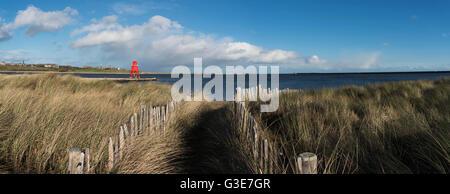 Pfad, gesäumt mit Holzpfosten und hohe Gräser an der Küste, Herde Buhne Leuchtturm in der Ferne; South Shields, - Stockfoto
