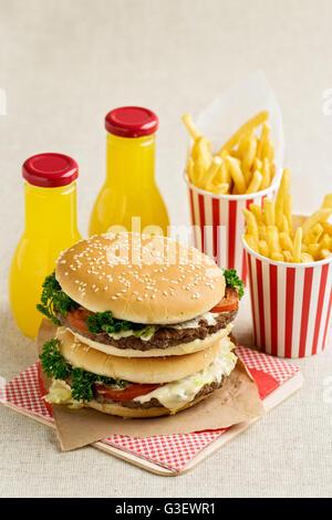 Burger mit Rindfleisch, Tomaten und Kräutern. Pommes Frites und Saft. Selektiven Fokus. - Stockfoto