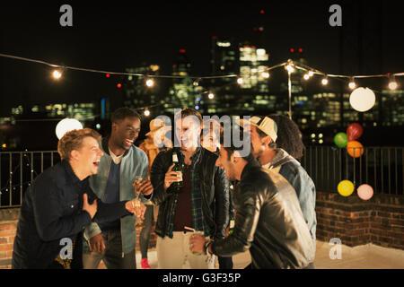 Junge Männer tranken und lachten auf Party auf dem Dach - Stockfoto