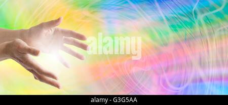 Farbe Heilung Webseite Banner - heilende Hände ausgestreckt mit einem wirbelnden Regenbogen-Energie-Hintergrund - Stockfoto