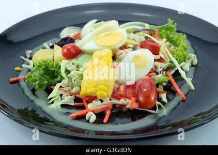 Salat mit Hühnerfleisch und Eiern auf schwarze Platte isoliert