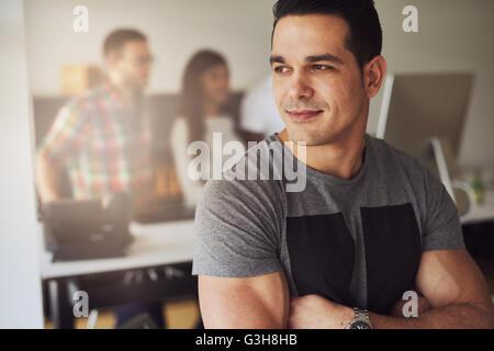 In der Nähe von ruhigen schönen männlichen Arbeitnehmer mit verschränkten muskulösen Arme tragen grau Kurzarm Shirt - Stockfoto