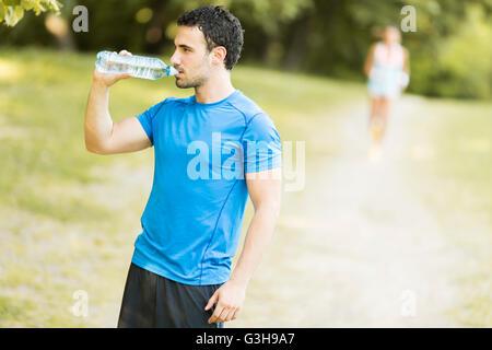 Athletische Sportart Man Trinkwasser aus der Flasche - Stockfoto
