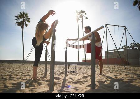 Paar am Strand ausüben, stretching, Gymnastik-Barren mit - Stockfoto