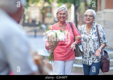 Zwei Reife Frauen tragen Blumenstrauß Arm in Arm in Stadt - Stockfoto