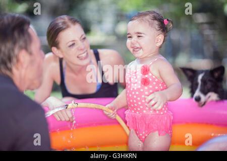 Eltern und Tochter in aufblasbaren Pool Hund auf - Stockfoto