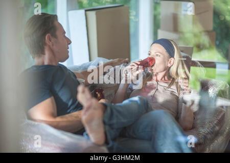 Umzug: paar entspannend auf sprudelte eingewickelt Sofa im Zimmer mit Kartons, Trinken von Champagner-Flöten - Stockfoto