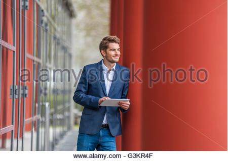 Mann in Jeans und Anzug Jacke gelehnt rote Säule mit digital-Tablette suchen Sie lächelnd - Stockfoto