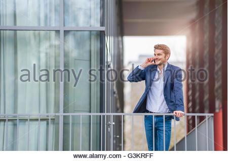 Mann gelehnt Geländer machen Telefonanruf entfernt lächelnd auf der Suche - Stockfoto