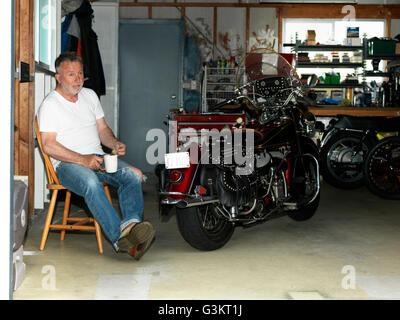 Senior Mann, sitzend mit einem Kaffee in der Garage mit Motorrad - Stockfoto
