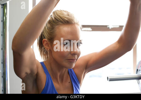 Frau im Fitness-Studio mit Heimtrainer - Stockfoto