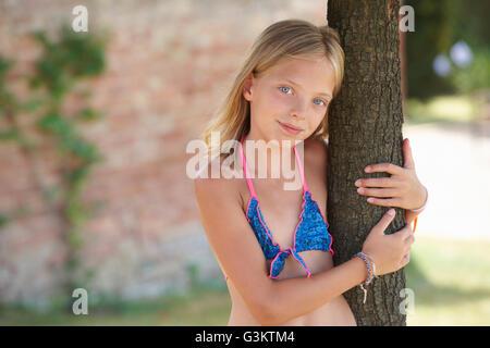 Porträt eines Mädchens tragen Bikini Top gelehnt Baum, Buonconvento, Toskana, Italien - Stockfoto