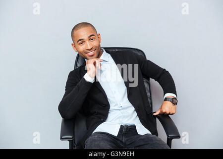 Zuversichtlich Lächeln auf den Lippen afroamerikanischen jungen Mann sitzen im Bürostuhl - Stockfoto