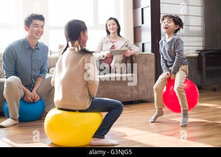 Glückliche junge Familie auf Hoppity Pferde zu Hause sitzen - Stockfoto