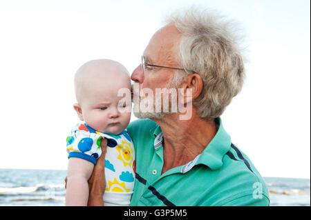Schweden, Mann halten und küssen Enkel (2-5 Monate) - Stockfoto