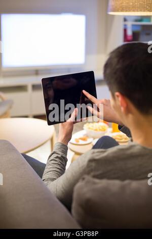 Junger Mann mit digital-Tablette auf Sofa im Wohnzimmer - Stockfoto