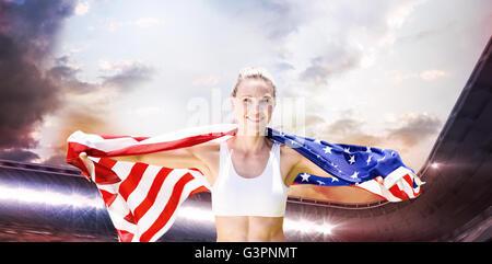 Zusammengesetztes Bild des Porträts von lächelnden Sportlerin posiert mit einer amerikanischen Flagge - Stockfoto