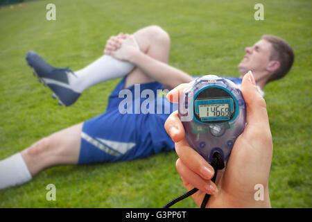 Zusammengesetztes Bild von einer Hand hält einen Timer gegen Football-Spieler in blau liegend verletzten - Stockfoto