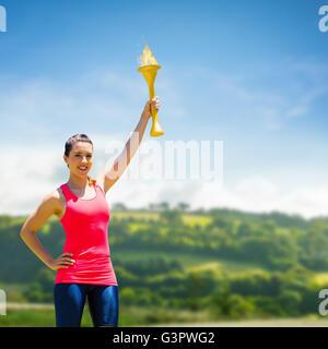 Zusammengesetztes Bild der sportlichen Frau posiert lächelnd mit Olympischen Fackel - Stockfoto