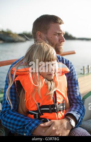Norwegen, Bergen, Mädchen (4-5) in Rettungsweste auf väterlichen Schoß sitzen