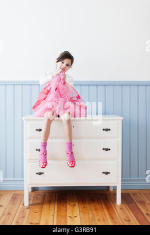 Schweden, kleines Mädchen im rosa Kleid sitzt auf Kommode (4-5)