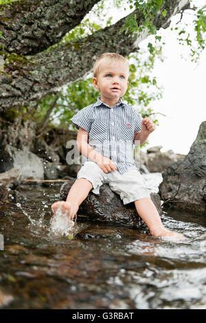 Schweden, Vastmanland, Baby Boy (18-23 Monate) Füße in Wasser eintauchen - Stockfoto