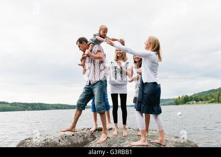 Schweden, Vastmanland, Bergslagen, Hällefors, Nygard, Familie mit vier Kindern auf Felsen - Stockfoto