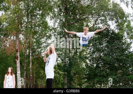 Schweden, Vastmanland, Bergslagen, Hällefors, Nygard, Kinder (10-11, 12-13, 14-15) gegen grüne Bäume - Stockfoto