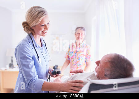 Arzt überprüft senior woman Blutdruck im Untersuchungsraum - Stockfoto