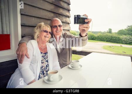 Großbritannien, England, Lincolnshire, Louth, Senior paar sitzt am Tisch auf der Veranda und unter Selfie mit Kamera - Stockfoto