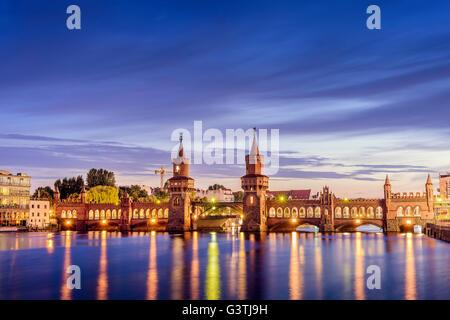 Deutschland, Berlin, Oberbaumbrücke beleuchtet und Reflexionen im Fluss - Stockfoto