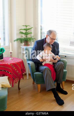 Finnland, Senior Mann sitzt im Sessel und Holding Enkel (18-23 Monate) auf runden - Stockfoto