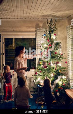 Finnland, Mutter mit Töchtern (12-17 Monate, 2-3, 4-5) schmücken Weihnachtsbaum - Stockfoto