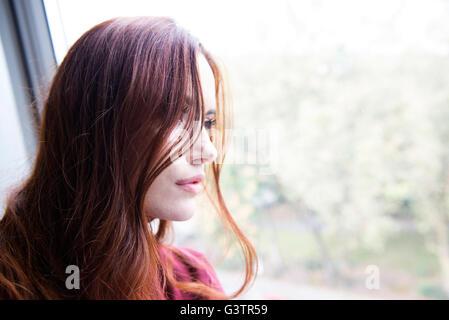 Porträt von einer attraktiven jungen Frau, die ein Fenster sitzen. - Stockfoto