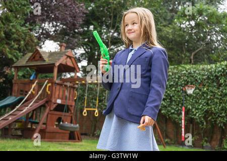 Ein zehnjähriges Mädchen in Schuluniform hält eine Wasserpistole. - Stockfoto