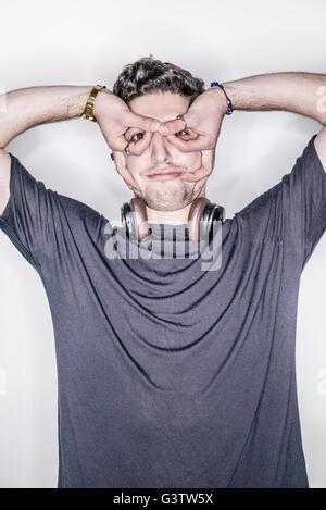 Ein junger Mann posiert in einem Studio machen Handgesten. - Stockfoto