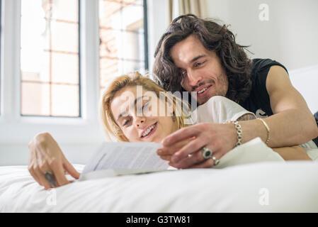 Ein cooles junges Paar liegend auf einem Bett, ein Buch zu betrachten. - Stockfoto