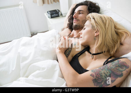 Eine coole junge tätowierte paar umfassend in einem Bett. - Stockfoto