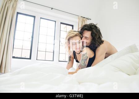 Eine coole junge tätowierte paar auf einem Bett kuscheln. - Stockfoto