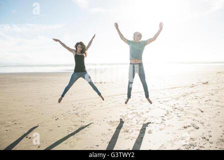 Ein junges Paar in der Sonne am Strand bei Porthmadog springen. - Stockfoto