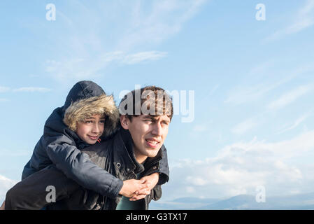 Ein Mann gibt seinem Sohn eine Huckepack am Strand von Porthmadog. - Stockfoto