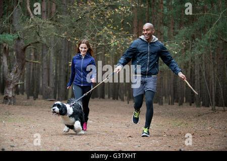 Ein junges Paar, mit ihrem Hund auf einem Waldspaziergang im Herbst. - Stockfoto