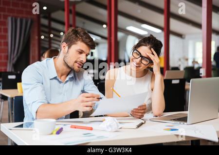 Lächelnde junge Geschäftspartnern zusammenarbeiten im Büro