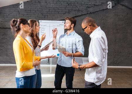 Multiethnische Gruppe von jungen Leuten im Konferenzraum stehen und brainstorming zusammen - Stockfoto