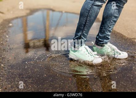 Frau in Detektive in einer Pfütze springen. Nahaufnahme der Füße in Schuhen mit Wasser spritzt - Stockfoto
