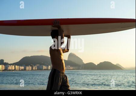 RIO DE JANEIRO - 5. April 2016: Ein junger brasilianischen Mann am Strand der Copacabana gleicht einem Surfbrett - Stockfoto