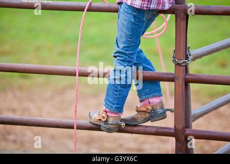 Ein Junge Cowgirl sitzt auf die Tore der Arena beim Rodeo - Stockfoto