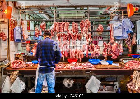 Hong Kong, China - 30. März 2015: Metzger schneiden Schweinefleisch für den Verkauf auf Gage Street in der Innenstadt - Stockfoto