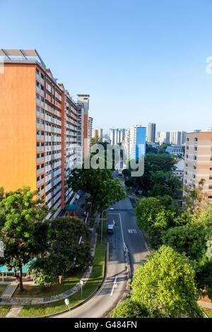 Eine Singapur Gehäuse Wohnsiedlung mit Mehrfamilienhäusern umgeben von Bäumen vor einem strahlend blauen Himmel. - Stockfoto